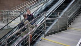 Het paar echtgenoten bevindt zich ondergronds op roltrap met bagage, in stock videobeelden