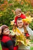 Het paar en het meisje verzamelen esdoorn doorbladeren in park stock afbeeldingen