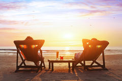 Het paar geniet luxe van zonsondergang op het strand royalty-vrije stock afbeeldingen