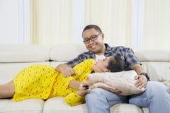 Het paar geniet van vrije tijd door op televisie te letten royalty-vrije stock afbeeldingen