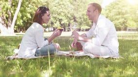 Het paar heeft een picknick in het park: de vrouw eet mango en een mens drinkt wijn stock videobeelden