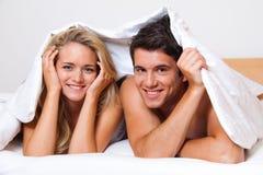Het paar heeft pret in bed. Gelach, vreugde en erotiek Stock Foto's