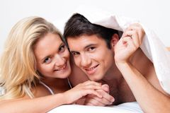 Het paar heeft pret in bed. Gelach, vreugde en erotiek Stock Afbeeldingen