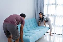 Het paar heft een bank op en beweegt zich aan nieuw huis stock fotografie
