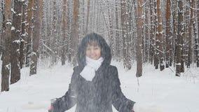 Het paar in het park in de winter werpt omhoog sneeuw in slowmotion stock video