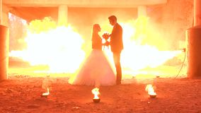Het paar in huwelijkskledij met een vreselijke make-up, op achtergrond brandt een reusachtige brand stock video