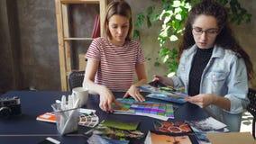 Het paar jonge ontwerpers kiest foto's voor belangrijk project Zij zetten beelden bij lijst en het bespreken stock footage
