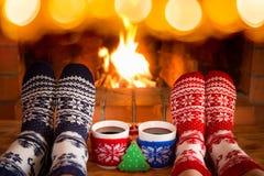 Het paar in Kerstmis mept dichtbij open haard stock afbeeldingen