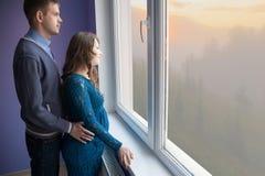Het paar kijkt uit het venster stock fotografie