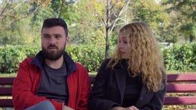Het paar komt de verhouding op de parkbank te weten stock footage