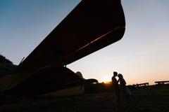 Het paar kust onder het uitstekende vliegtuig Royalty-vrije Stock Afbeeldingen