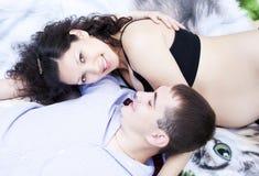 Het paar legt samen, koesterend, zwangere vrouw Stock Fotografie