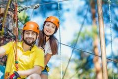 Het paar in liefde geniet van actieve vrije tijd in extreem kabelpark royalty-vrije stock foto's