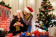 Het paar in liefde in hoeden bij Kerstmis geeft elkaar giften E Stock Foto's