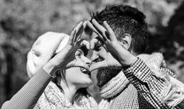 Het paar in liefde met sjaals maakt hart met vingers ondertekenen stock afbeelding