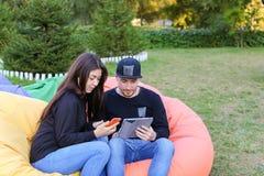 Het paar in liefde zit en spreekt in leunstoelen, houdt de kerel in hand elec Royalty-vrije Stock Foto