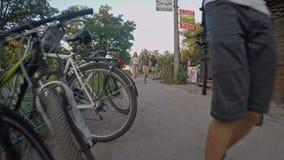 Het paar in liefdeholding overhandigt heel wat mensen en fietsen, de video van kerelspruiten stock videobeelden