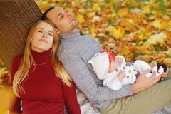 Het paar in liefdezitting op de herfst gevallen bladeren in een park, zit dichtbij een boom, genietend van een mooie de herfstdag stock afbeelding