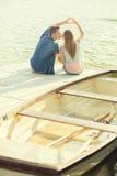 Het paar in liefdezitting op de pijler, hun handen toont hart Stock Foto