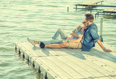 Het paar in liefdezitting op de pijler, omhelst royalty-vrije stock foto