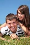 Het paar ligt op gras stock afbeeldingen