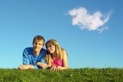 Het paar ligt op weide met wolk Stock Foto