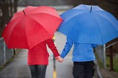 Het paar loopt hand in hand in de regen met paraplu Stock Afbeeldingen