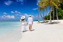 Het paar loopt onderaan een tropisch strand in de eilanden van de Maldiven royalty-vrije stock afbeelding