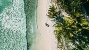 Het paar loopt op het strand tussen de oceaan en de palmen royalty-vrije stock afbeeldingen