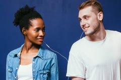 Het paar luistert samen muziek, één oortelefoon voor twee royalty-vrije stock afbeelding