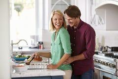 Het paar maakt de Maaltijd van Braadstukturkije samen in Keuken stock fotografie