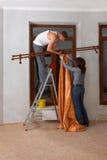 Het paar maakt reparatie. Hang omhoog een kroonlijst Royalty-vrije Stock Afbeeldingen