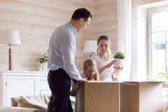 Het paar met dochter pakt hun bezittingenbeweging bij nieuw huis uit stock fotografie