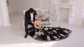 Het paar met een griezelige Halloween-make-up zit op een uitstekende bank in een uitstekende ruimte stock video