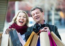 Het paar met het winkelen doet in openlucht in zakken Royalty-vrije Stock Fotografie