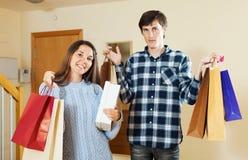 Het paar met het winkelen doet thuis in zakken Stock Foto's