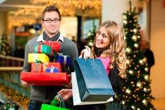 Het paar met Kerstmis stelt en doet in wandelgalerij voor in zakken Stock Afbeelding