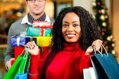 Het paar met Kerstmis stelt en doet in wandelgalerij voor in zakken Royalty-vrije Stock Foto