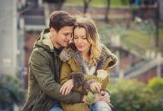 Het paar met nam in liefde het kussen op straatsteeg het vieren Valentijnskaartendag toe met hartstochtszitting op stadspark Royalty-vrije Stock Afbeelding