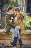 Het paar met nam in liefde het kussen op straatsteeg het vieren Valentijnskaartendag toe met hartstochtszitting op stadspark Royalty-vrije Stock Fotografie