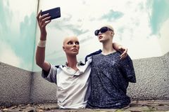 Het paar modellen neemt een selfie gekleed in cl van de de jaren '70sportkleding stock afbeeldingen