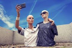 Het paar modellen neemt een selfie gekleed in cl van de de jaren '70sportkleding stock afbeelding