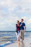 Het paar neemt een gang bij Duits Noordzeestrand Stock Foto