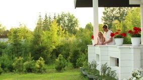 Het paar omhelst op de veranda van een buitenhuis stock footage