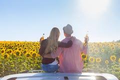 Het paar omhelst van het dakzonnebloemen van de zittingsauto het gebiedszonsopgang royalty-vrije stock foto