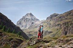 Het paar omhelste het bekijken het bergachtige landschap van de Italiaanse Alpen stock foto