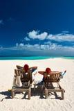 Het paar ontspant op een strand bij Kerstmis Royalty-vrije Stock Afbeeldingen