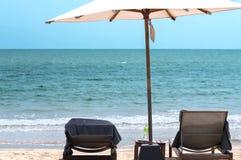 Het paar ontspant op het strand onder reuzeparaplu Royalty-vrije Stock Foto's