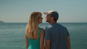 Het paar op fotospruit bij kust lopen, die geniet van ogenblikken kussen stock videobeelden