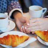Het paar in Parijse koffie, het drinken koffie met croissants en het houden van elkaar overhandigt stock afbeelding